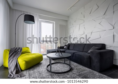 Living room with green sack couch, round table, sofa and 3d wall decor #1013546290