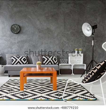 Living room with grey walls and white wooden parquet. Black and white decorations with orange coffee table in the middle of the room - Shutterstock ID 488779210
