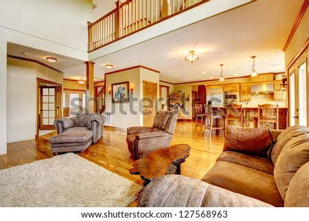 Living room with high ceiling, kitchen and leather sofa.
