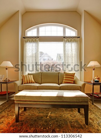 Living room with large window and classic sofa with table.