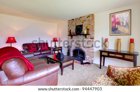 Living room with leather sofas and fireplace with pink blankets