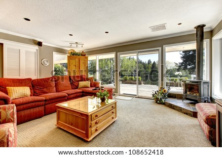 Living room with many windows, red sofa and stove.