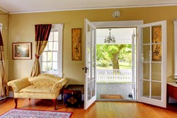 Living room with open doors to the front porch. Romantic classic with park view.