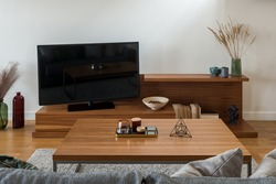 Living room with television screen on wooden sideboard with many stylish decorations and big, wooden coffee table with ornaments
