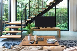 Living room with TV stairs, wooden shelves The view is a natural tree.