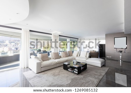 Living room with white leather sofa and windows overlooking the city of Lugano in Switzerland. Nobody inside
