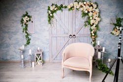 Living room with white sofa and many different flowers. Spring interior in a photo studio with flowers and a classic sofa. Background for photo shoot
