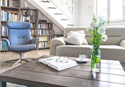 Living room wooden table with white roses, coffee cup and book