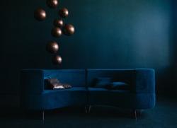 livingroom with blue velvet sofa. golden and blue pillows. sphere bronze lamps. modern interior in blue tones.