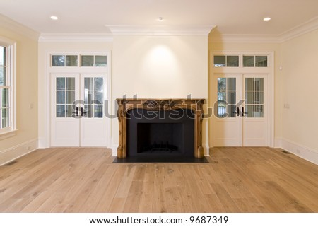 livingroom with intricately carved fireplace and lots of doors and windows