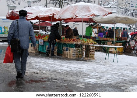 LJUBLJANA, SLOVENIA-DECEMBER 8:Vendor sells apples on his stall in first day of snow in Ljubljana, Slovenia, on December 8, 2012. In spite the snow market is still full of fruits and vegetables. - stock photo