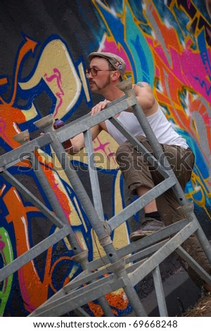 LJUBLJANA, SLOVENIA - JUNE 19: Graffiti artist climbing the scaffold to get higher and paint  wall on June 19, 2010 in Ljubljana, Slovenia. Traditional event Night in Museum takes place till midnight