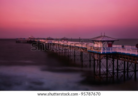 Llandudno pier at dusk with purple-red sky, North Wales - stock photo