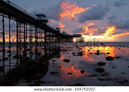 Llandudno Sunrise with low tide under the pier and the clouds light up