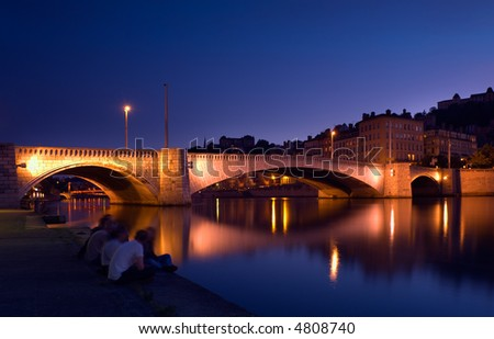 llluminated bridge over the river Saone in the city of Lyon, France, with a group of young people  having a friendly chat by the river