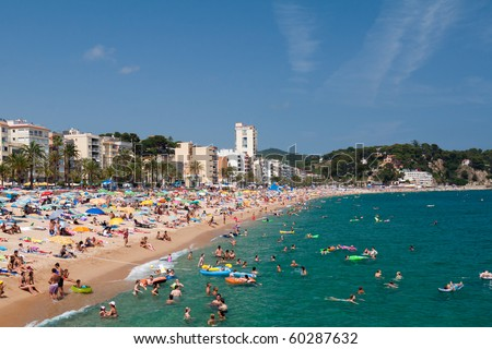LLORET DE MAR, SPAIN-JULY 8: People swim and sunbathe at the city beach of Lloret de Mar on July 8, 2010 in Lloret de Mar, Spain. The beach is one of the most popular holiday resorts in Spain