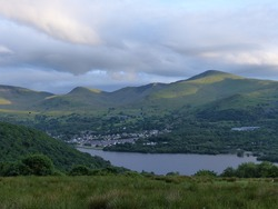 Llyn Padarn (Lake), Llanberis, Caernarfon, Snowdonia, North Wales, Europe. 12 June 2016. Beautiful landscape of welsh mountains with grey red colors in the sky, mountains, hill and the river and lake.