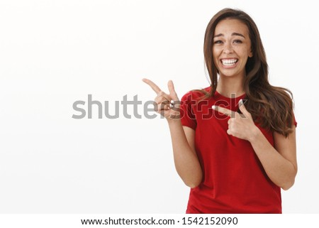 Lmao very funny. Amused and carefree cute carefree brunette woman in red t-shirt having fun, smiling joyfully pointing left at blank white copy space, laughing out loud enjoy humorous stand-up #1542152090