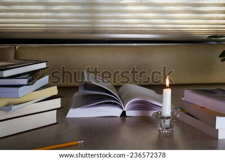 load of books on a candle light lit table with nobody studying