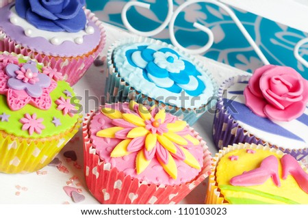 Load of cupcakes in different colors with flower decoration