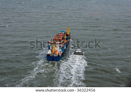 Loaded Cargo ship headed out to sea with pilot boat beside.