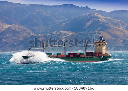 Loaded container freighter ship sailing in stormy ocean with tall and heavy breakers still near shore