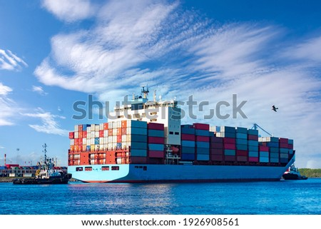 Loaded container ship. Ship with colorful containers on Board. Shipping. Transportation of goods by sea.Container ship and tug in the sea commercial port.