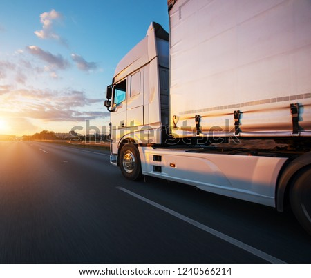Loaded European truck on motorway in beautiful sunset light. On the road transportation and cargo. #1240566214