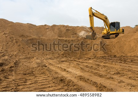Loader backhoe parked there on the mountain, which has a large pile of sand in the wheel tracks below.