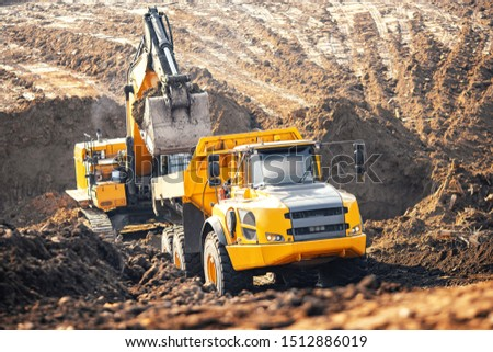 Loader excavator during earthmoving works loads soil ground into large yellow dump truck. Concept open mine. Foto stock ©