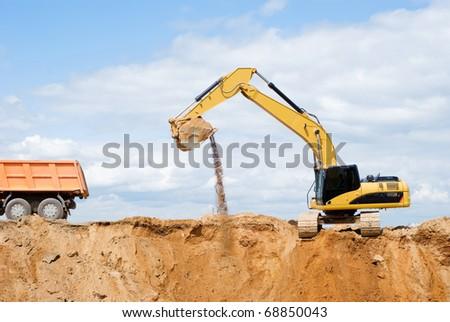 Loader Excavator loading body of a dump truck tipper at open cast over blue sky in summer