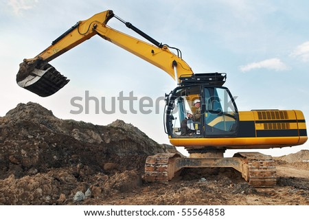 Loader Excavator standing in sandpit with risen bucket over cloudscape sky