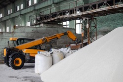 Loader loading jumbo-bags with white urea fertilizer in the warehouse. Selective focus.