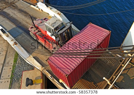 loader with container entering the oceanic ferry ship - stock photo
