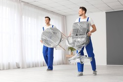 Loaders carrying furniture in flat
