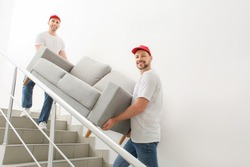 Loaders carrying furniture in the stairway