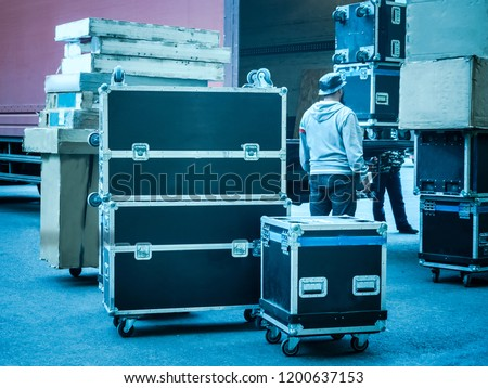 Loading and unloading of concert equipment. Loading equipment in a van. Man controls the loading of equipment cases.