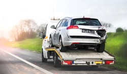 Loading broken car on a tow truck. Damage vehicle after crash accident on the highway road.