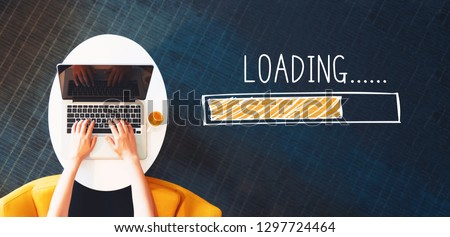 Loading concept with person using a laptop on a white table #1297724464