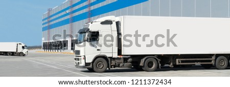 Loading dock of large warehouse with white truck under loading with yellow separators #1211372434