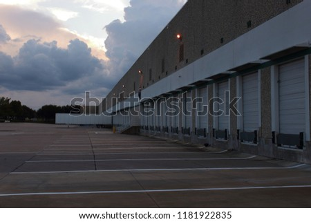 Loading docks in the evening , The lights of the building just came on.Truck drivers will soon back into these doors and get all of their freight loaded or unloaded. #1181922835
