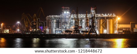 Loading grain in the port. Night panoramic view of the port, cranes and other port infrastructure. #1218448672