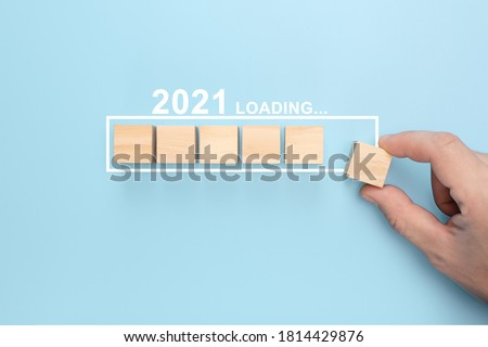 Loading new year 2021 with hand putting wood cube in progress bar. creative background for the new year. Loading new year 2021 concept Stock photo ©