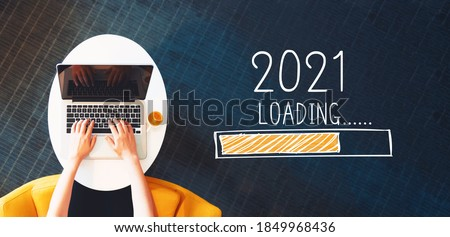Loading new year 2021 with person using a laptop on a white table