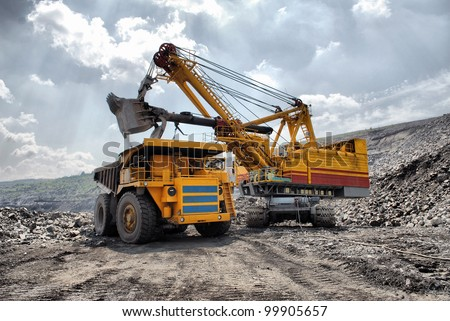 Loading of iron ore on very big dump-body truck HDR