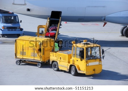 Loading of luggage in an airplane on an airport - stock photo