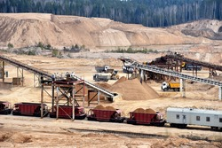 Loading sand into freight cars of a train in quarry. Sand Making Plant in open-pit mining. Crushing factory, machines and equipment for crushing, grinding stone, sorting sand and bulk materials