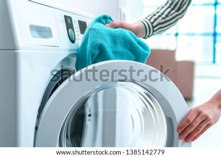 Loading towel, clothes and linen in washing machine. Doing laundry at home. Household chores and housekeeping #1385142779