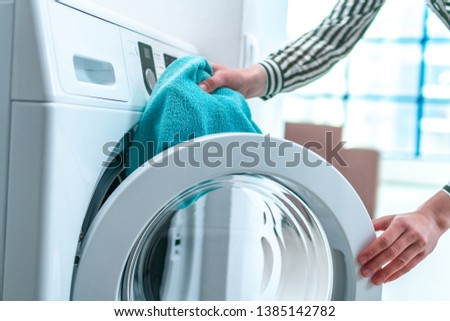 Loading towel, clothes and linen in washing machine. Doing laundry at home. Household chores and housekeeping #1385142782