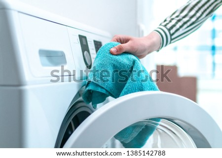 Loading towel, clothes and linen in washing machine. Doing laundry at home. Household chores and housekeeping #1385142788